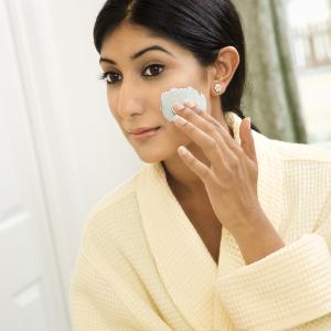 Close up of young Asian/Indian woman applying facial scrub.